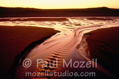 The sun sets of the outgoing tide at the Parker River National Wildlife Refuge on Plum Island, Newbury, Massachusetts (Paul Mozell)