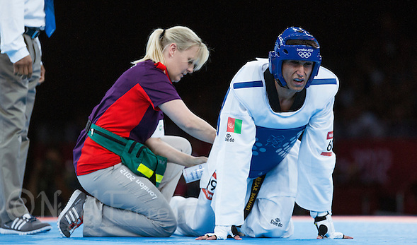 10 AUG 2012 - LONDON, GBR - Nesar Bahawi (AFG) (right) of Afghanistan receives treatment during his men's -80kg category preliminary round contest against Issam Chernoubi of Morocco at the London 2012 Olympic Games Taekwondo at Excel in London, Great Britain (PHOTO (C) 2012 NIGEL FARROW) (NIGEL FARROW/(C) 2012 NIGEL FARROW)