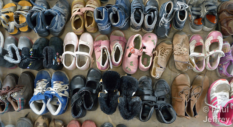 Donated shoes await child refugees at the border crossing into Austria near the Hungarian town of Hegyeshalom. Hundreds of thousands of refugees and migrants--including many children--flowed through Hungary in 2015 on their way to western Europe from Syria, Iraq and other countries. (Paul Jeffrey)
