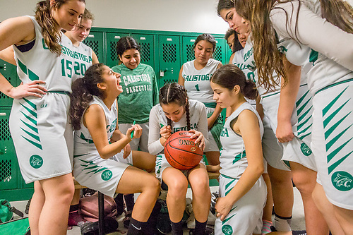 The Calistoga High School Women's Basketball team signs the game ball on the night when senior Gilda Roas (green shirt) scored her 1000th career point. (Clark James Mishler)