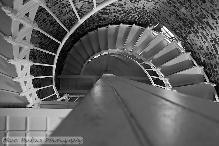 A view from the bottom of the stairway leading to the top of Point Sur Light Station's lighthouse's lantern room.  I'm a total sucker for lighthouse stairways ? the white iron stairway contrasts beautifully with the wooden central beam and brick exterior (with light streaming in through a window). (Marc C. Perkins)