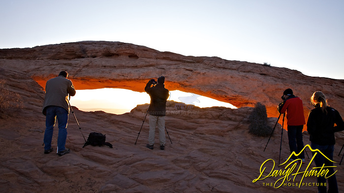 "Photographers gather around Mesa  Arch in Canyonlands National Park to  capture the magic of its legendary glow. (Daryl Hunter's ""The Hole Picture"" ? Daryl L. Hunter has been photographing the Yellowstone Region since 1987, when he packed up his view camera, Pentex 6X7, and his 35mm?s and headed to Jackson Hole Wyoming. Besides selling photography Daryl also publishe)"
