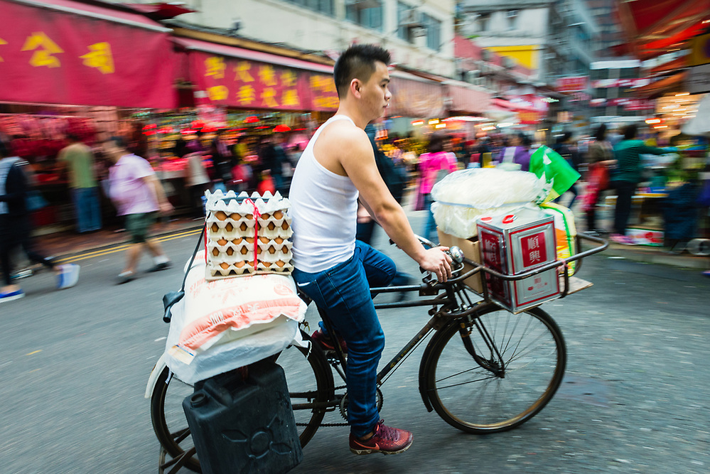 Man delivering goods on bicycle at Bowrington Road wet market, Hong Kong (Mark Eden)