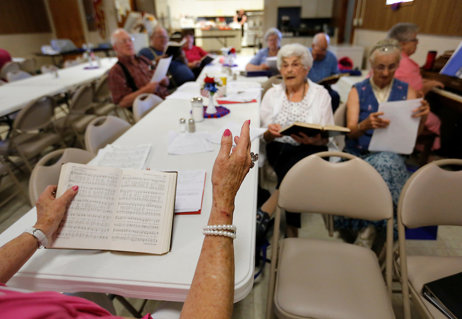 Mary Jane Narigon, 82, of Elston directs a group of seniors as they sing hymns together at the Tingley Community Center on August 1, 2014.  The center serves as a meal site for the elderly to enjoy some fellowship and lunch together. (Christopher Gannon/The Register)
