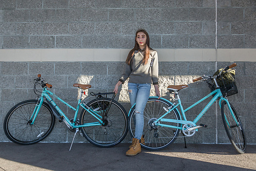 """I can't wait to get a bike lock so I dont have to guard these bikes.""  -High school freshman Laila Loray guards Christmas present bicycles as she waits for her sister to return from inside the Office Depot in Santa Rosa, CA (Clark James Mishler)"