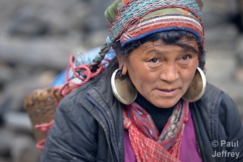 A woman carries a heavy load through the Tamang village of Goljung, in the Rasuwa District of Nepal near the country's border with Tibet. (Paul Jeffrey)