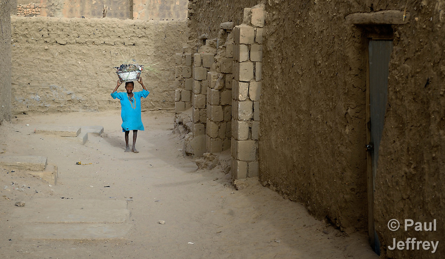Carrying a bucket of trash on his head, a boy walks along a street in Timbuktu, the northern Mali city that was seized by Islamist fighters in 2012 and then liberated by French and Malian soldiers in early 2013. (Paul Jeffrey)