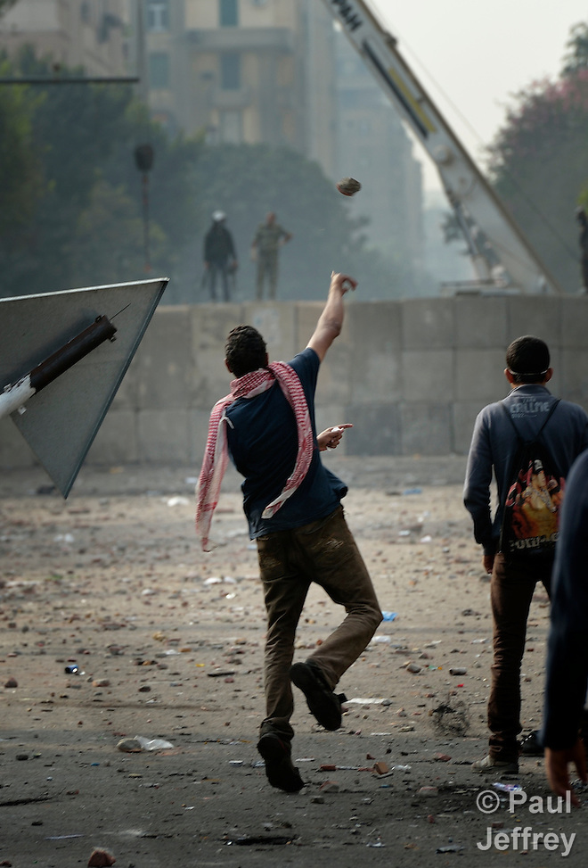 A man throws a rock toward police during November 25, 2012, protests in and around Cairo's Tahrir Square. The protestors were upset by Egyptian President Mohammed Mursi's November 22nd decision to assume sweeping new powers.