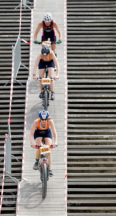 13 JUL 2013 - DEN HAAG, NED - Sylvia Visser (NED) (bottom) of the Netherlands  leads competitors down a ramp during the 2013 ITU Age Group Cross Triathlon World Championships in Kijkduin, Den Haag (The Hague), the Netherlands (PHOTO COPYRIGHT © 2013 NIGEL FARROW, ALL RIGHTS RESERVED) (NIGEL FARROW/COPYRIGHT © 2013 NIGEL FARROW : www.nigelfarrow.com)