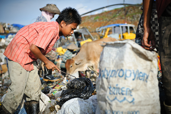 Taupik, 14, working alongside other trash pickers on the 'Trash mountain', Makassar, Sulawesi, Indonesia. (Matthew Oldfield)