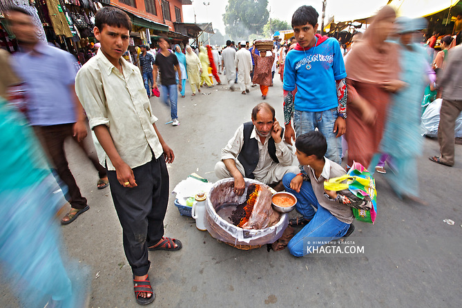 A vendor sells a local snack in the middle of the road to Hazratbal Shrine.  Devotees converged for peace prayers at the famous Muslim shrine of Hazratbal to mark Meraj-ul-Alam festival in Srinagar, Prophet Mohammed's Moi-e-Muqaddas (Holy Relic) is displayed for public viewing on ten occasions in a year, which includes Meraj-ul Alam. (Himanshu Khagta)