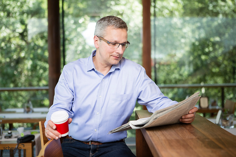 Österreich, Portrait Mann / Geschäftsmann, an Theke eines Restaurants, Zeitung lesend, Kaffeepause, Casual Look, Pause, Entspannung (dieter schewig)
