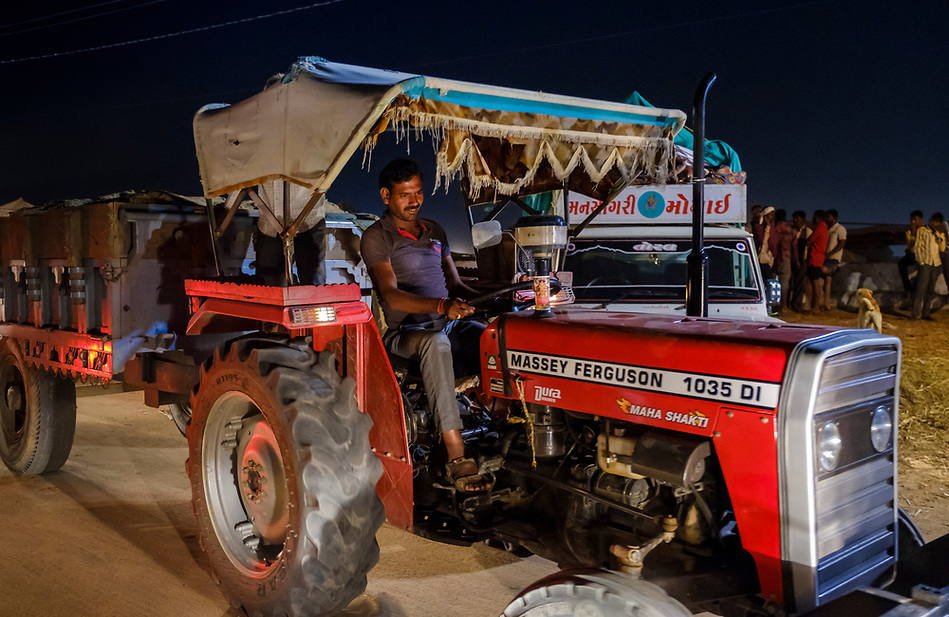PUSHKAR, INDIA - CIRCA NOVEMBER 2016: Man driving a tractor at night during the Pushkar Camel Fair. It is one of the world's largest camel fairs. Apart from the buying and selling of livestock, it has become an important tourist attraction. (Daniel Korzeniewski)