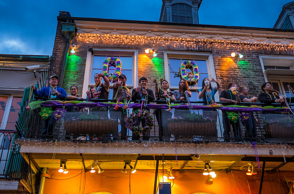 NEW ORLEANS - CIRCA FEBRUARY 2014: People showing Mardi Gras beads in balcony over Bourbon Street in the New Orleans French Quarter in Louisiana, at night. (Daniel Korzeniewski)