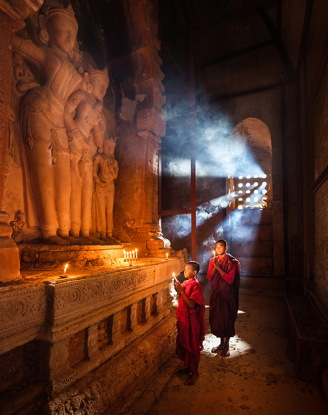 BAGAN, MYANMAR - CIRCA DECEMBER 2017: Monks inside a temple with candlelights praying. (Daniel Korzeniewski)