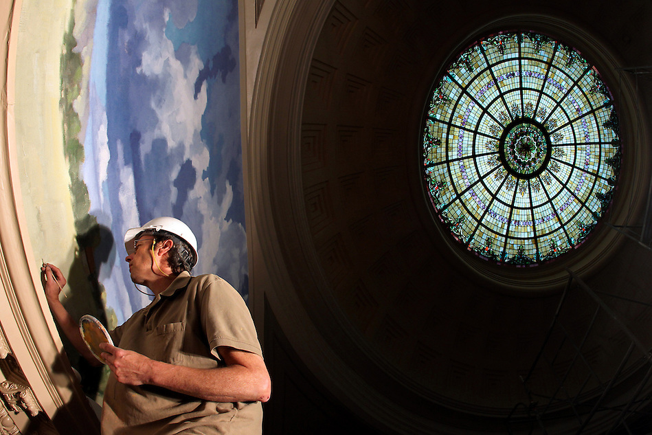 Working atop 35-foot scaffolding, Rick Van Oel of  Evergreene Archictural Arts places a few careful touch-up brush strokes upon a newly-installed mural as restoration work continues inside the Dr. Norman E. Borlaug Hall of Laureates in Des Moines.  Serving as headquarters for the World Food Prize, and as a special tribute to Dr. Norman Borlaug, the World Food Prize has embarked on a $29.8 million capital project to restore the century-old Des Moines Public Library Building as the Dr. Norman E. Borlaug Hall of Laureates. (Christopher Gannon/The Register)
