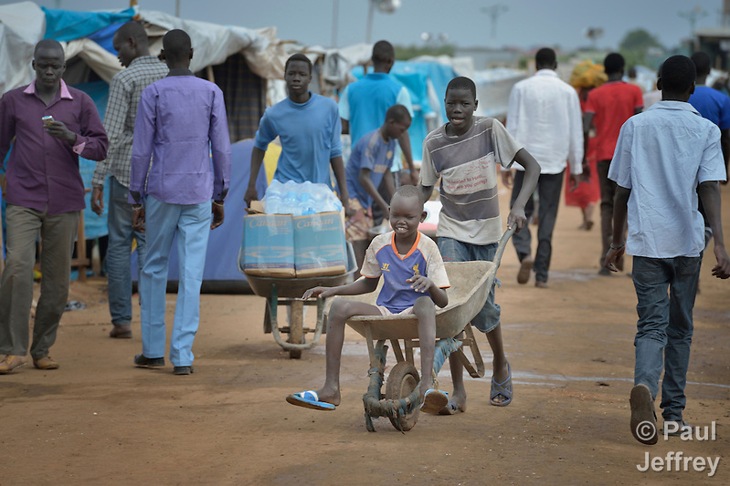 A boy gets a ride in a wheel barrow on a street in a camp for internally displaced families located inside a United Nations base in Juba, South Sudan. The camp holds Nuer families who took refuge there in December 2013 after a political dispute within the country's ruling party quickly fractured the young nation along ethnic and tribal lines. The ACT Alliance is providing a variety of services, including fresh water, sanitation and refuse collection services, to the more than 20,000 people living in the camp. (Paul Jeffrey)