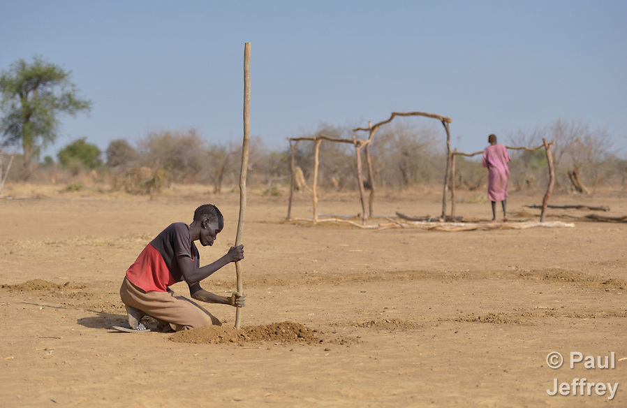 Amon Akuel Aler digs holes where she hopes to insert poles to begin the construction of a shelter in the internally displaced persons camp in Turalei, South Sudan. Families started arriving here shortly after fighting broke out in December 2013, and new families continued to arrive in March 2014 as fighting continued. Many are living in the open and under trees. The ACT Alliance is providing the displaced families and the host communities affected by their presence with a variety of support, including new wells. This woman has not seen her husband since the fighting began, and was separated from two of her five children as they fled Bentieu. She has not located them yet. (Paul Jeffrey)