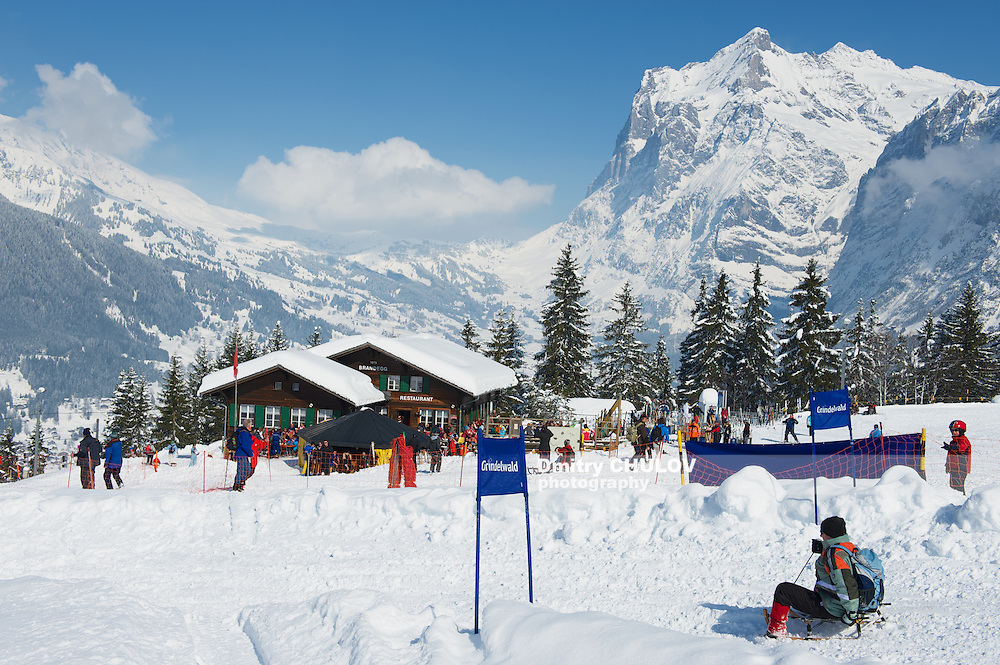 GRINDELWALD, SWITZERLAND – MARCH 07, 2009: Unidentified tourists relax at the Brandegg ski station in Grindelwald, Bernese Alps, Switzerland. Grindelwald area is a famous ski resort in Switzerland. (Dmitry Chulov)