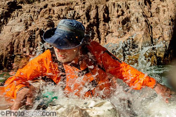 Glenn gets splashed fafting the Inner Gorge between Colorado River Miles 97-108. Day 7 of 16 days rafting 226 miles down the Colorado River in Grand Canyon National Park, Arizona, USA. (© Tom Dempsey / PhotoSeek.com)