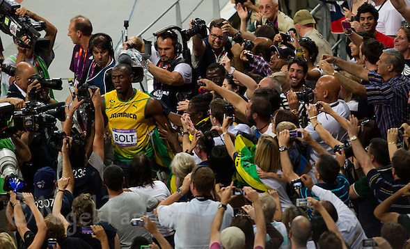 09 AUG 2012 - LONDON, GBR - Usain Bolt (JAM) (top left in yellow and green) of Jamaica walks back to the track after celebrating winning the men's 200m final with his mother Jennifer Bolt during the London 2012 Olympic Games athletics at the Olympic Stadium in Stratford, London, Great Britain (PHOTO (C) 2012 NIGEL FARROW) (NIGEL FARROW/(C) 2012 NIGEL FARROW)