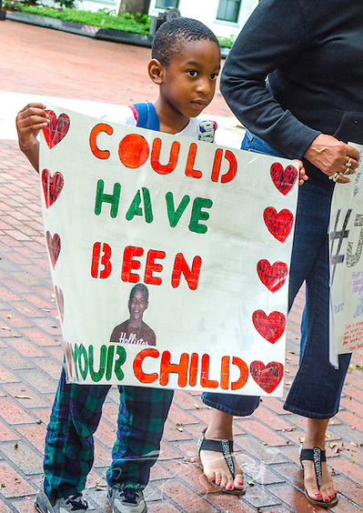 "Sevyn Coleman, 5, stands outside the Florida Capitol building in Tallahassee, July 20, 2013, holding a sign featuring an image of 17-year-old Trayvon Martin, who was fatally shot in early 2012. Coleman was with his mother, Dana Coleman, who was participating in a rally against racial profiling and Florida's ""stand-your-ground"" self-defense law.  (Photo by Carmen K. Sisson) (Carmen K. Sisson/Cloudybright)"
