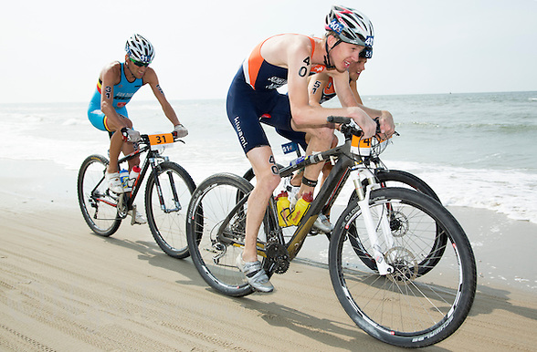 13 JUL 2013 - DEN HAAG, NED - Cornelis Scheltinga (NED) (second from the left, #40, in dark blue and orange) of the Netherlands races along the beach with Jarrich Van Woersem (NED) (right #51, in dark blue and orange) also of the Netherlands and Tim Van Daele (BEL) (left) of Belgium during the 2013 ITU Cross Triathlon World Championships in Kijkduin in Den Haag (The Hague), the Netherlands (PHOTO COPYRIGHT © 2013 NIGEL FARROW, ALL RIGHTS RESERVED) (NIGEL FARROW/COPYRIGHT © 2013 NIGEL FARROW : www.nigelfarrow.com)