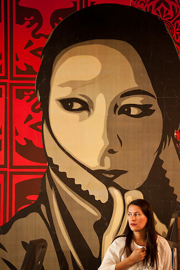 Store manager, Sue Carey, with Shephard Fairey poster in Zebreaclub retail outlet, Seattle. (Clark James Mishler)