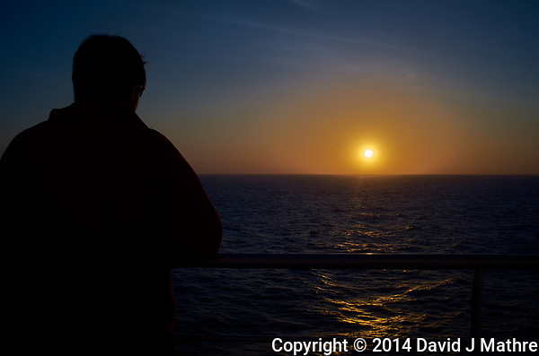 Silhouette of a student watching the sun set over the Atlantic Ocean from the deck of the MV Explorer. Image taken with a Leica X2 camera. (David J Mathre)