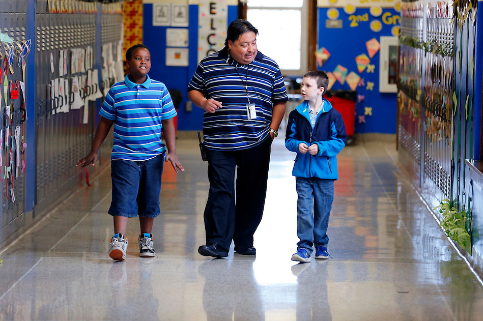 "Carlos Alonzo, center, a SUCCESS Case Manager with Des Moines Public Schools, walks a corridor with third graders Yussuf Yussuf, 9, left, and Zachary Thompson, 8, at Willard Elementary School on April 2. ""I try to give them my time instead of things,"" Alonzo says of his relationship building approach. (Photo by Christopher Gannon) (Christopher Gannon)"
