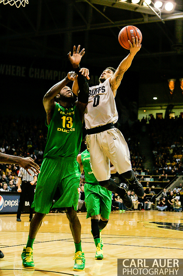 January 5th, 2014:  Colorado Buffaloes junior guard Askia Booker (0) is fouled by Oregon Ducks redshirt senior forward Richard Amardi (13) as he attempts a lay up in the first half of the NCAA Basketball game between the Oregon Ducks and the University of Colorado Buffaloes at the Coors Events Center in Boulder, Colorado (Carl Auer/ZUMAPRESS.com)