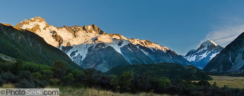 Sunrise brightens Mount Sefton (left) and Aoraki / Mount Cook (right) in Aoraki / Mount Cook National Park, South Island, New Zealand. In 1990, UNESCO honored Te Wahipounamu - South West New Zealand as a World Heritage Area. Panorama stitched from 3 overlapping photos. (© Tom Dempsey / PhotoSeek.com)
