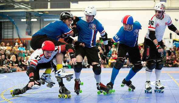 16 MAR 2014 - BIRMINGHAM, GBR - Team England jammer Sully (bottom left) tries to escape a challenge from Team France blocker Angry Bear during the inaugural Men's Roller Derby World Cup at the Futsal Arena in Birmingham, West Midlands, Great Britain (PHOTO COPYRIGHT © 2014 NIGEL FARROW, ALL RIGHTS RESERVED) (NIGEL FARROW/COPYRIGHT © 2014 NIGEL FARROW : www.nigelfarrow.com)