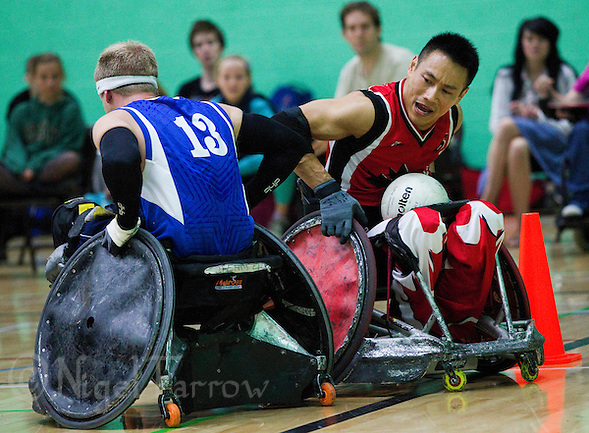 15 AUG 2011 - LEEDS, GBR - Canada's Ian Chan brushes off a challenge from Great Britain's Aaron Phipps to score during the wheelchair rugby exhibition match between the two teams .(PHOTO (C) NIGEL FARROW) (NIGEL FARROW/(C) 2011 NIGEL FARROW)