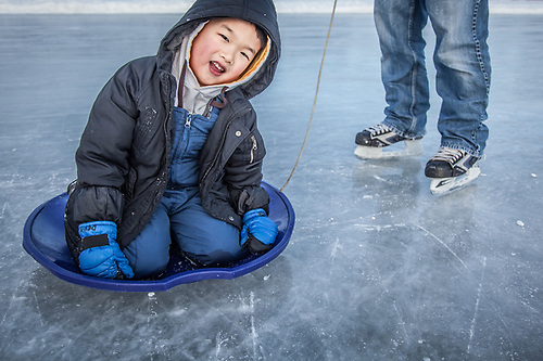 "Anchorage fireman Jae Lee and his five year old son, Devin, at Westchester Lagoon, Anchorage  ""He didn't want to skate and then he wasn't crazy about the sled…eventually, he started to enjoy it.""  leej159@hotmail.com (© Clark James Mishler)"