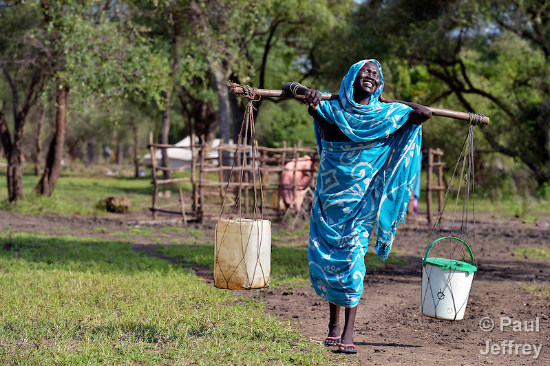 A woman laughs as she carries water through the Gendrassa refugee camp in South Sudan's Upper Nile State. More than 110,000 refugees were living in four camps in Maban County in October 2012, but officials expected more would arrive once the rainy season ended and people could cross rivers that block the routes from Sudan's Blue Nile area, where Sudanese military has been bombing civilian populations as part of its response to a local insurgency. Conditions in the camps are often grim, with outbreaks of diseases such as Hepatitis E. (Paul Jeffrey)