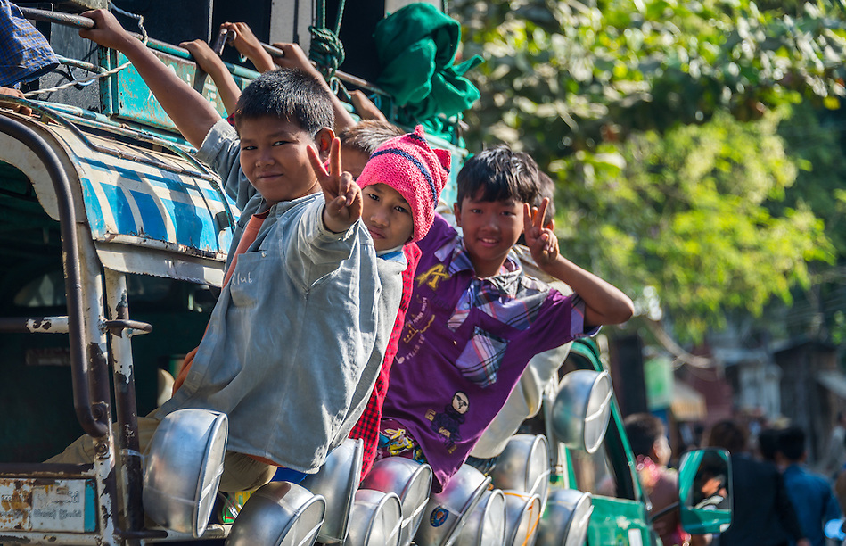 MANDALAY, MYANMAR - CIRCA DECEMBER 2013: Happy Burmese children riding a typical bus in the streets of Amarpura in Myanmar (Daniel Korzeniewski)