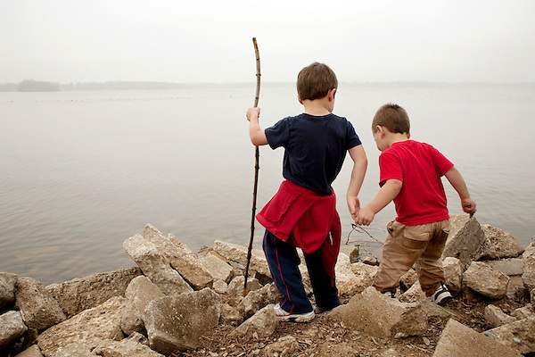 My older son, then five, helps his younger brother, then two, out to the edge of Lake Springfield in Illinois. (Kristen Schmid / Millennium Images UK)