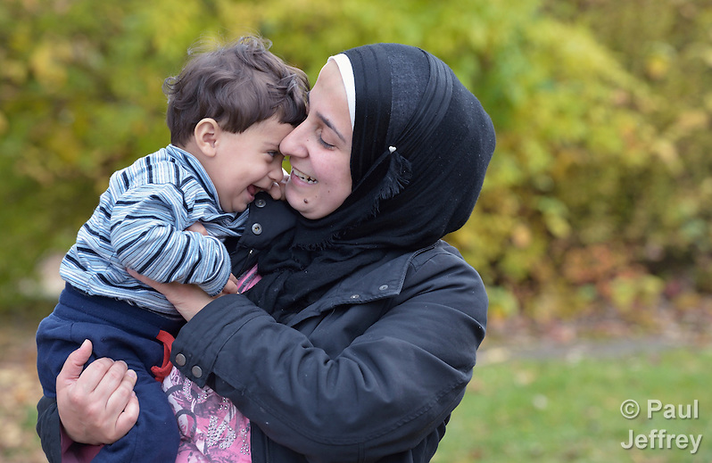 Farhan Othman holds her 9-month old son Mohammed in Messstetten, Germany. Refugees from Syria, they and their family have applied for asylum in Germany and are awaiting word on the government's decision. Meanwhile, they live in a room in a former army barracks in Messstetten. (Paul Jeffrey)