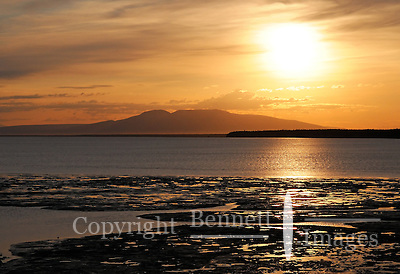 The sun sets behind Mt. Susitna, also known as Sleeping Lady, on a summer evening across Cook Inlet from Anchorage, Alaska. (Edward Bennett)