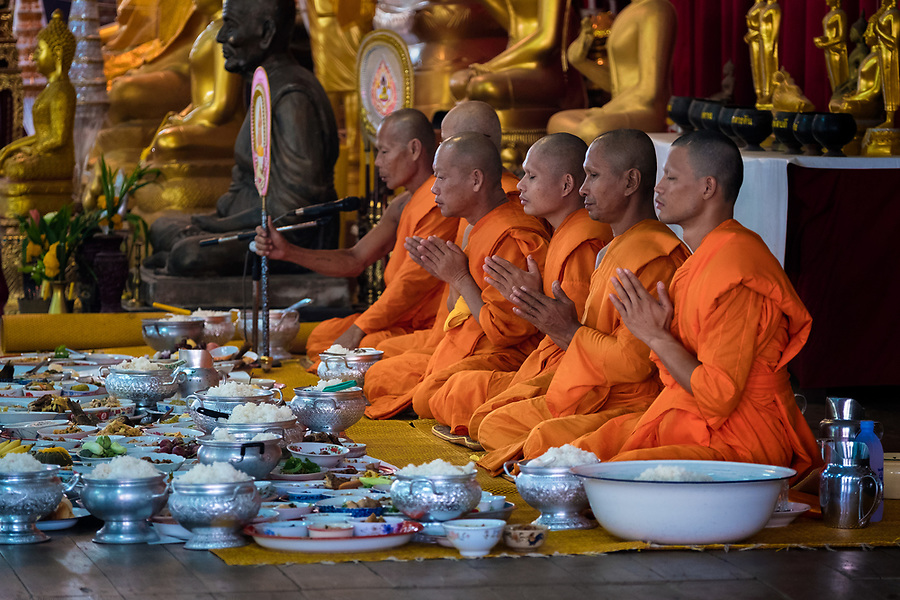 Breakfast is presented to monks at the local temple as a way of giving alms to make merit. The monks will bless the food and will eat first, then the meal will become potluck for the congregation to enjoy. (Lee Craker/Lee Craker, Photographer)
