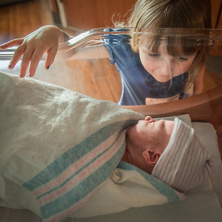 First touch.  Three year old granddaughter Mya leans in to touch her six hour old brother, Lucas. (© Clark James Mishler)