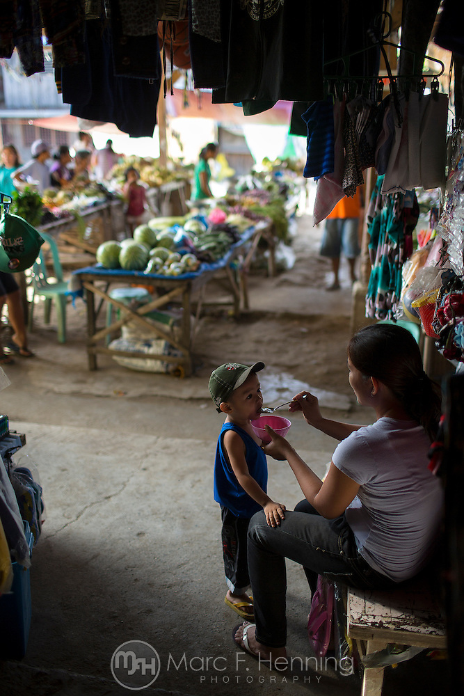 Photo by Marc F. Henning A mother feeds her child breakfast while tending to her shop on April 24, 2014, in the early morning at the Central Market in Mansalay, Oriental Mindoro, Philippines. (MARC F. HENNING/MARC F. HENNING PHOTOGRAPHY)