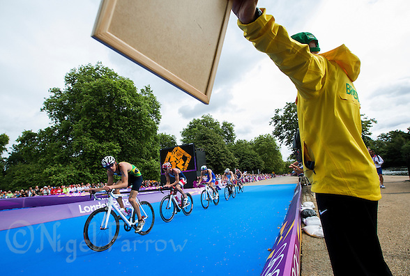 07 AUG 2012 - LONDON, GBR - Brazilian coach Sergio Santos (in yellow) shouts bike split times to Diogo Sclebin (BRA) of Brazil (left) during the men's London 2012 Olympic Games Triathlon in Hyde Park in London, Great Britain (PHOTO (C) 2012 NIGEL FARROW) (NIGEL FARROW/(C) 2012 NIGEL FARROW)