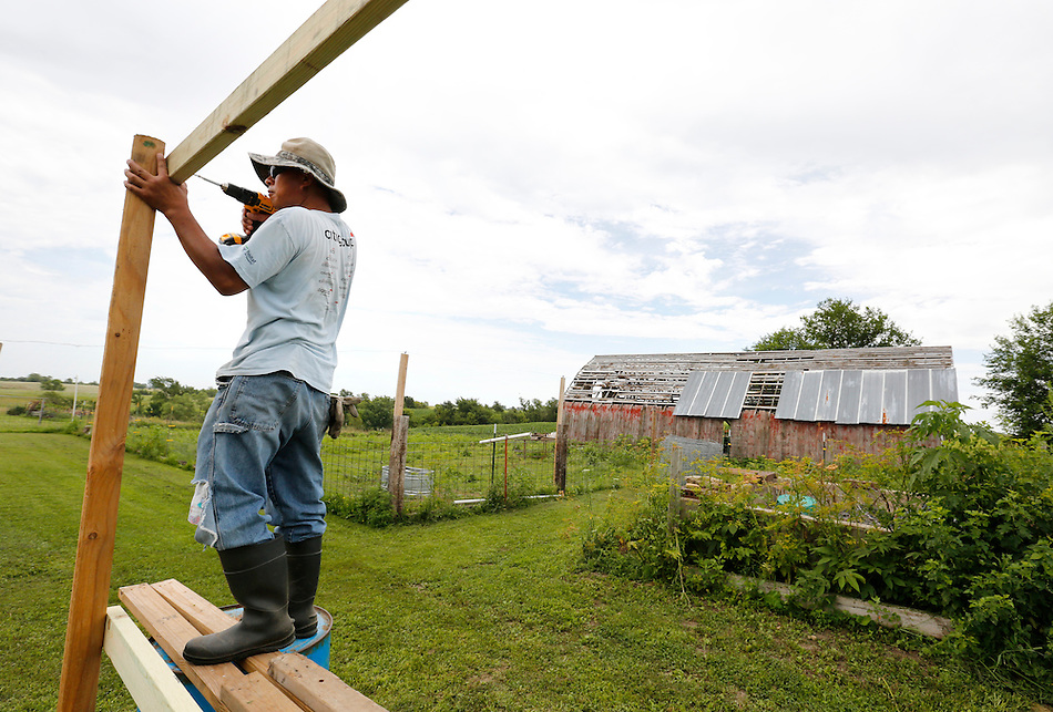 "Farmer Phrakhounmany ""Air"" Philavanh is building his own duck houses on his farm near Milo.  A Laotian immigrant, Philavanh remembers his grandfather's farm in Loas and has always wanted to farm in America.  He is raising cattle and plans to raise duck, a popular food among the Laotian people. (Christopher Gannon/The Register)"