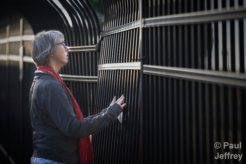 The Rev. Mary Kohlstaedt Huycke prays at the fence surrounding the Federal Detention Center in Seatac, Washington, during a June 24 prayer vigil in support of immigrant parents inside the prison who've been separated from their children. Huycke is district superintendent of the Seven Rivers District of the United Methodist Church. (Paul Jeffrey)