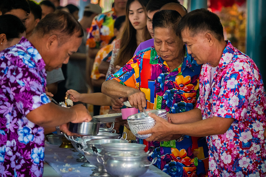 Members of the congregation fill rice bowls that will be presented to the monks on the first day of Songkran in rural Nakhon Nayok, Thailand. (Lee Craker/Lee Craker, Photographer)