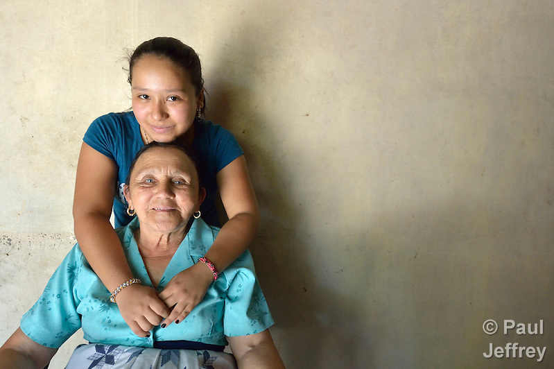 Aleska Garcia, 17, poses with her grandmother, Petronila Reyes, at their home in Goascoran, Honduras. The teenager left Honduras in June 2014 to travel north to be with her mother, who lives in the United States, but she was detained by Mexican law enforcement officials and returned to Honduras. For now she says she wants to remain at home and finish her high school studies. (Paul Jeffrey)