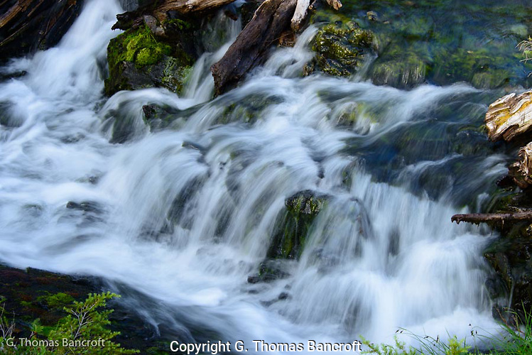 The water spread across a shallow stream before tumbling over a series of rocks.  Water droplets bounced off rocks as they continued downstream.  The softness was mesmerizing and the sound soothing. (G. Thomas Bancroft)