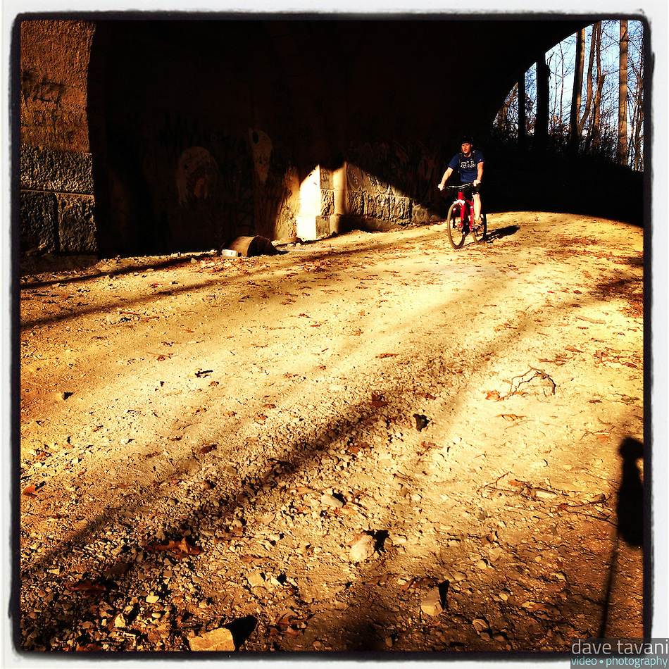 A mountain biker rides into the light after passing underneath the Henry Avenue Bridge on December 5, 2012. (Dave Tavani)